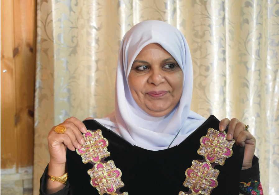 HUSANYA IBN BARI holds up a hand-embroidered garment that she designed and made