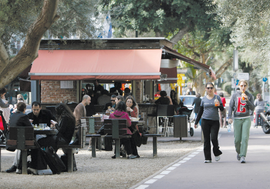 PEOPLE WALK past a cafe in Tel Aviv