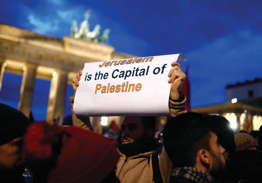 A PROTESTER holds a placard during the demonstration outside the US embassy in Berlin against Presid
