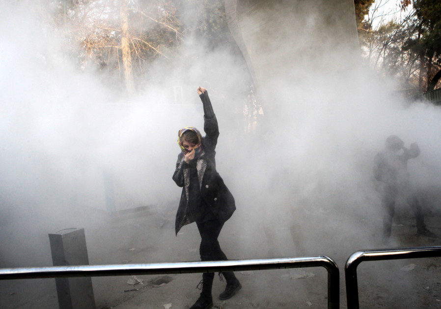 An Iranian woman raises her fist during a protest on December 30, 2017