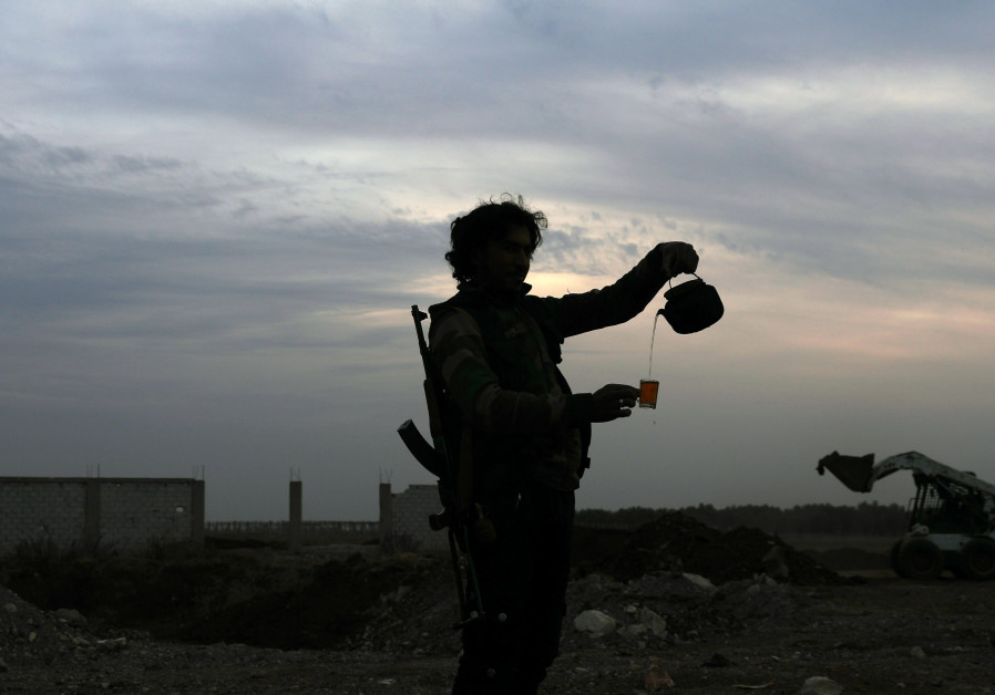 A Free Syrian army fighter pours tea in the rebel-held town of Dael, Syria.