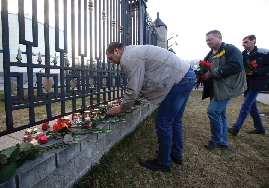 Men lay flowers at a cemetery to commemorate victims of the St. Petersberg metro blast