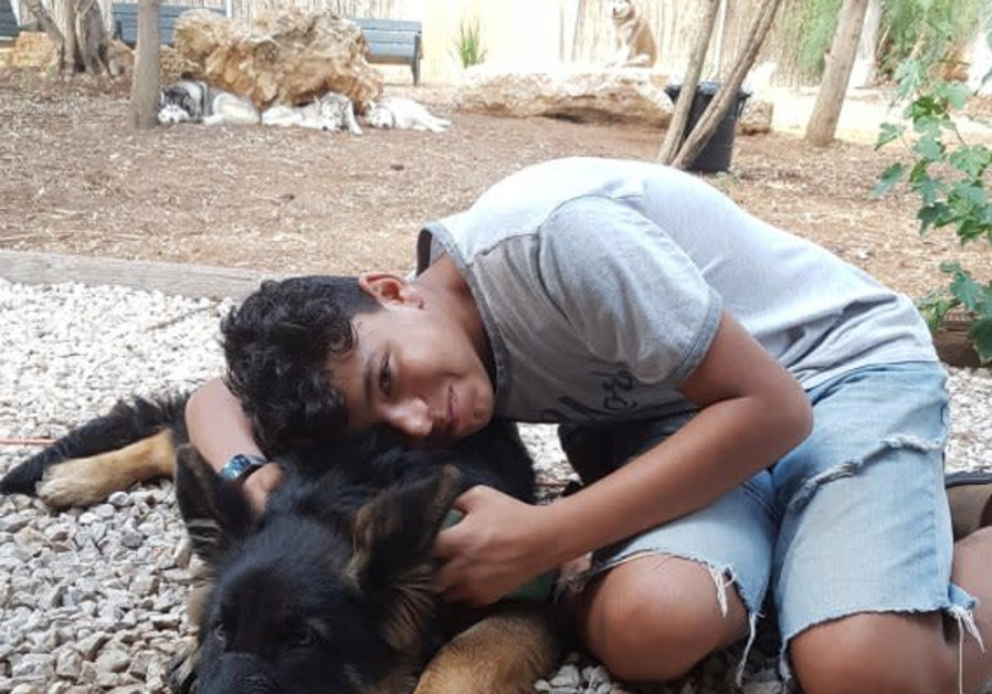 Lidor, a member of the Hadassah Ne'urim Youth village, poses with one of the dogs being rehabilitate