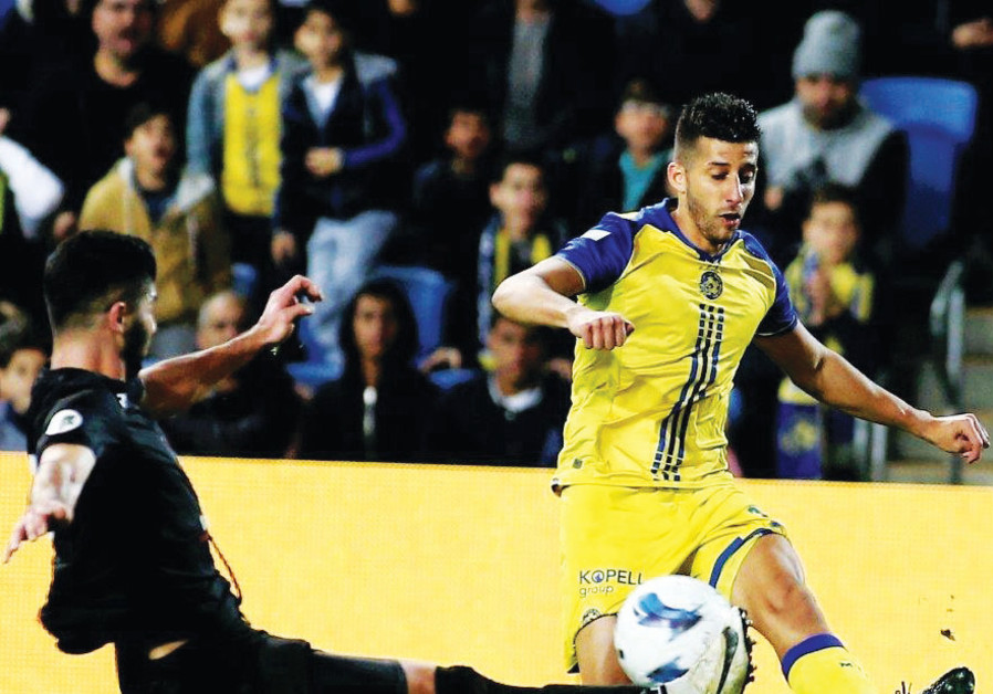 Two days after signing a four-year contract extension, Maccabi Tel Aviv midfielder Dor Micha (right)