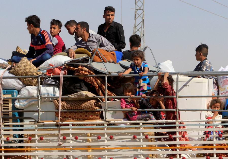 Displaced people riding in trucks and cars head back to their homes in Hawija, on the outskirts of K