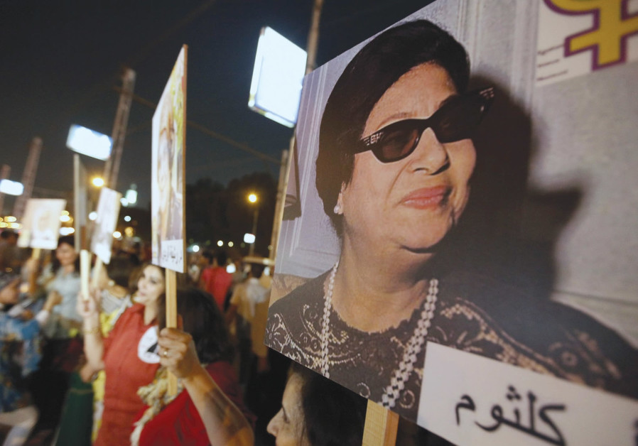 WOMEN CARRY photos of the late Egyptian singer Oum Kalthoum, who despite writing songs that included
