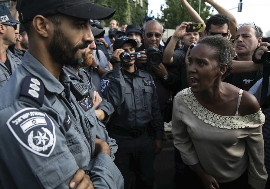 AN ETHIOPIAN PROTESTER shouts at a policeman during a demonstration in Tel Aviv against what protest