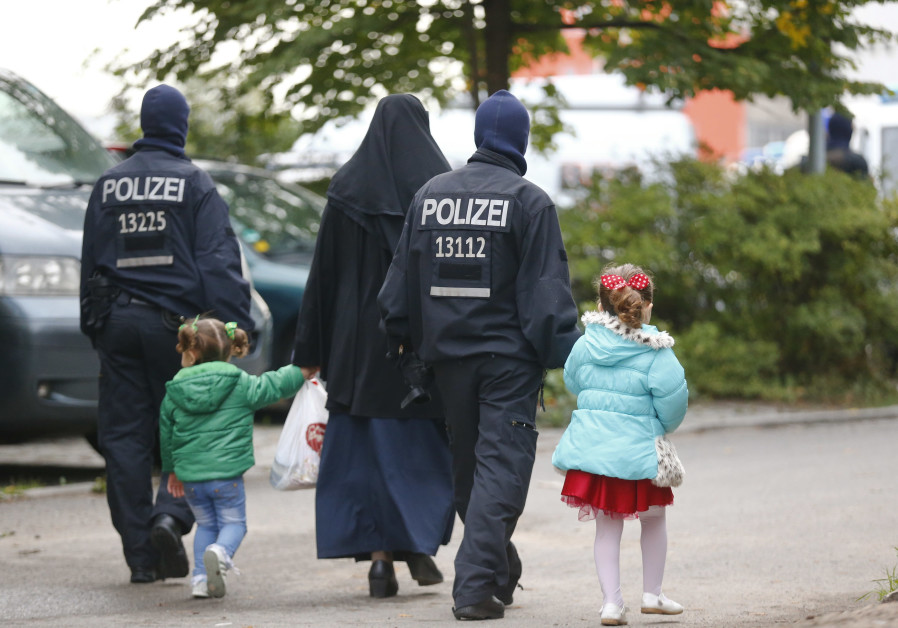 German security forces walk with a Muslim family outside a mosque in Berlin