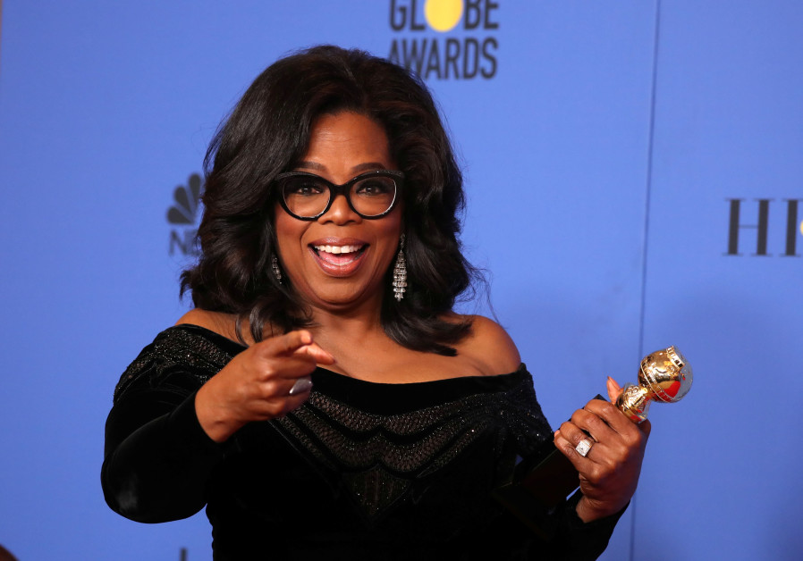 Oprah Winfrey poses backstage with her Cecil B. DeMille Award