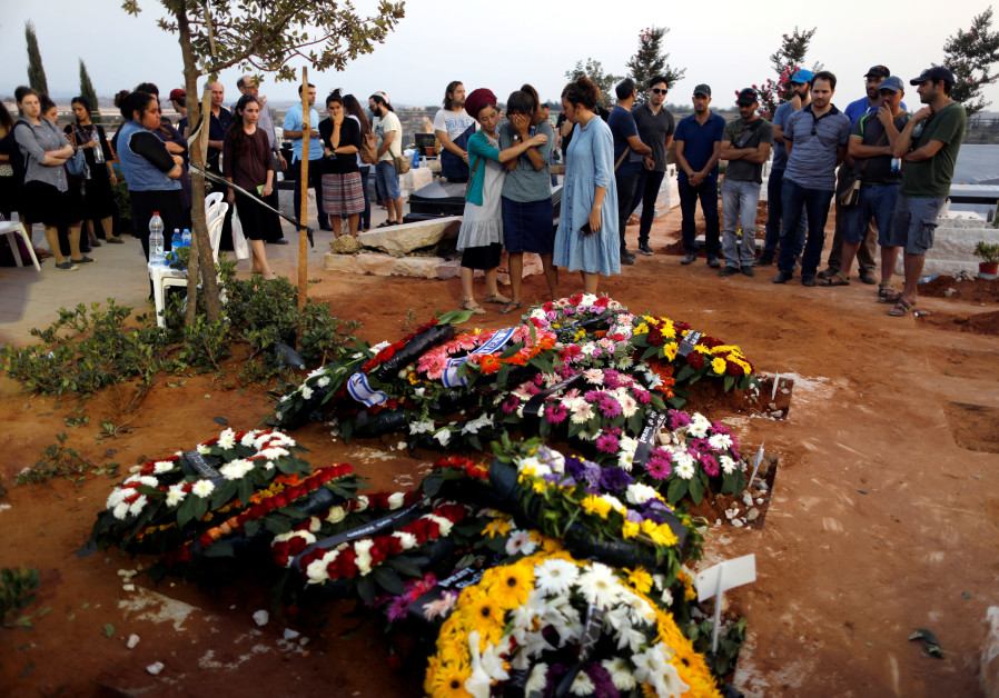 Family and friends mourn around the fresh graves of Haya, Elad and Yossi Salomon