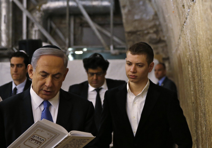 Yair Netanyahu observes his father Israeli Prime Minister Benjamin Netanyahu reading a prayer at the