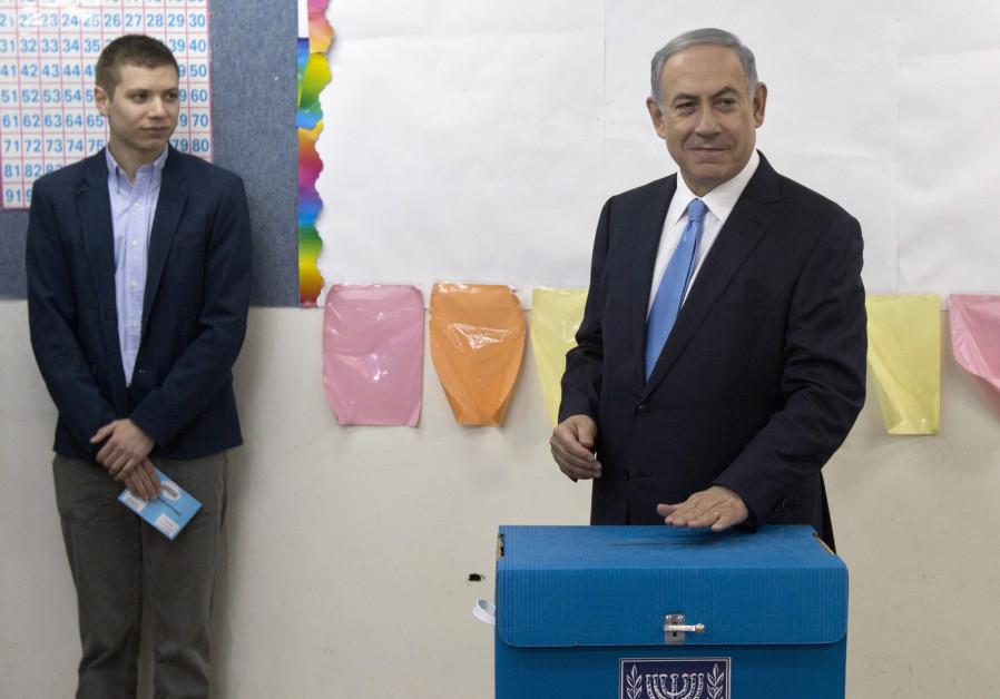 Yair Netanyahu observes his father Israeli Prime Minister Benjamin Netanyahu casting a ballot in the