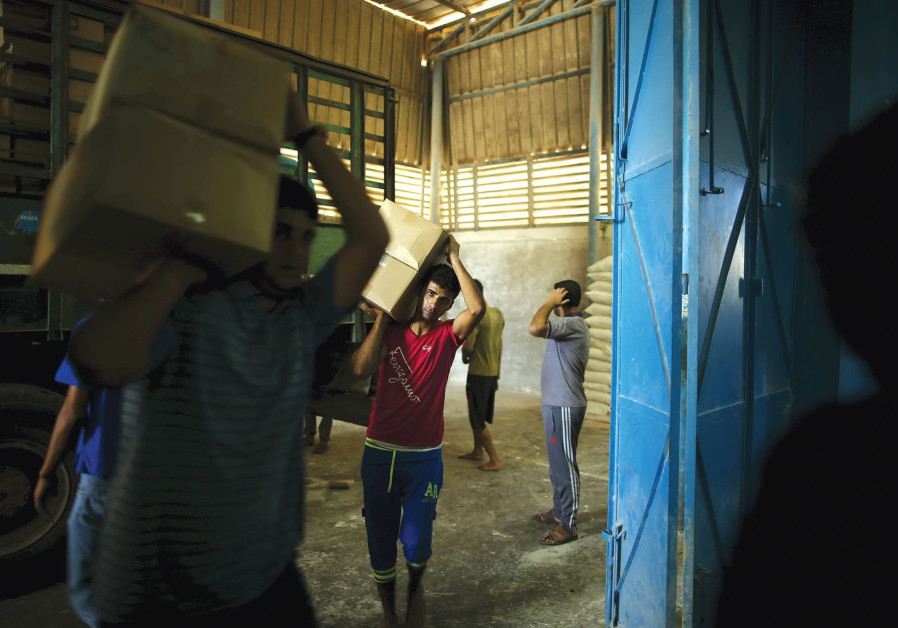WORKERS CARRY boxes containing food supplies for Palestinian refugees at a United Nations Relief and