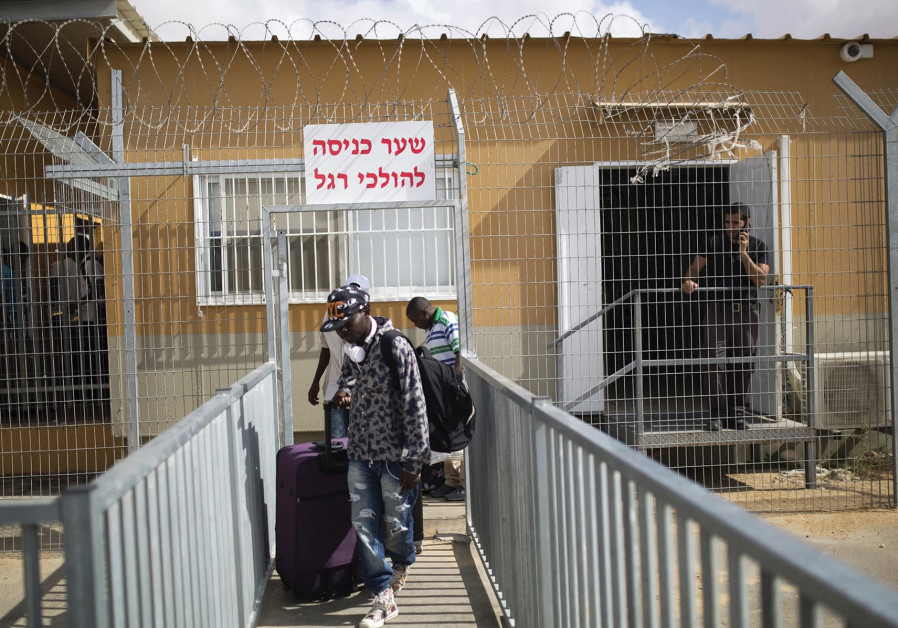 AFRICAN MIGRANTS walk with their luggage as they leave Holot detention center in the Negev in 2015.