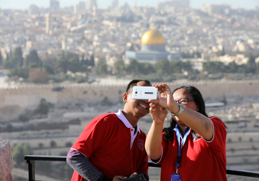 Tourists look at a mobile phone as they stand at an observation point overlooking Jerusalem