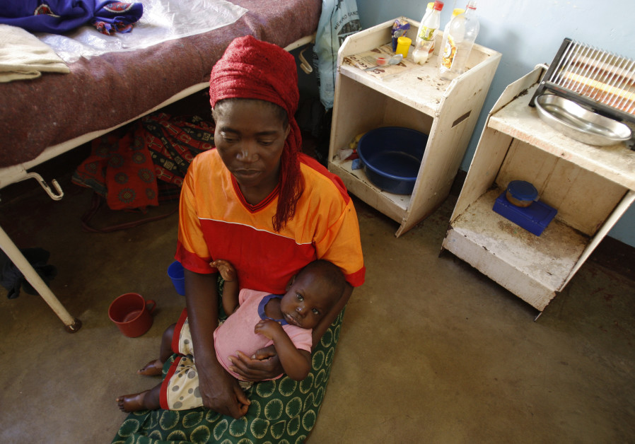 A Zambian woman holds her child at the paediatric section of the General Hospital (FILE)