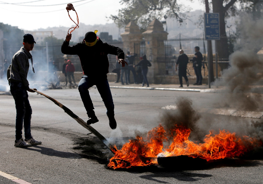 A Palestinian demonstrator jumps over a burning tire in a protest in Bethlehem, January 2018