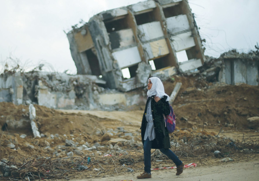 A GIRL WALKS by the remains of a house in the northern Gaza Strip that was destroyed.