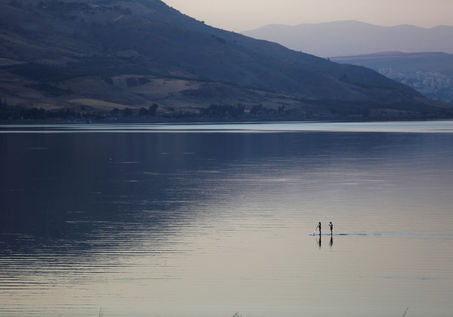 PEOPLE PADDLE on stand-up boards in Lake Kinneret