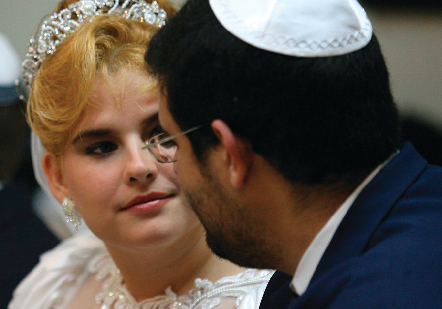 A COUPLE looks at each other while waiting to get married at Havana's Beth Shalom synagogue in 2007
