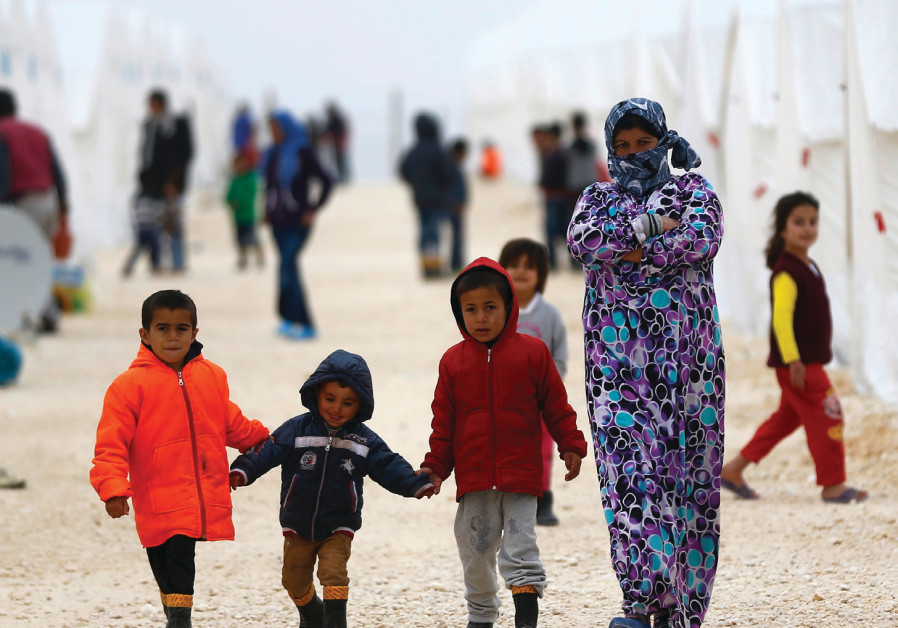 DISPLACED SYRIANS walk in a refugee camp in the Turkish border town of Suruc in January 2015