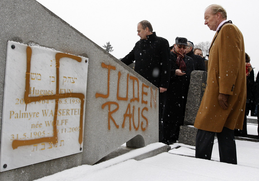 "A tombstone desecrated by vandals with a Nazi swastika and the Slogan ""Jews Out"", in the Jewish Ceme"
