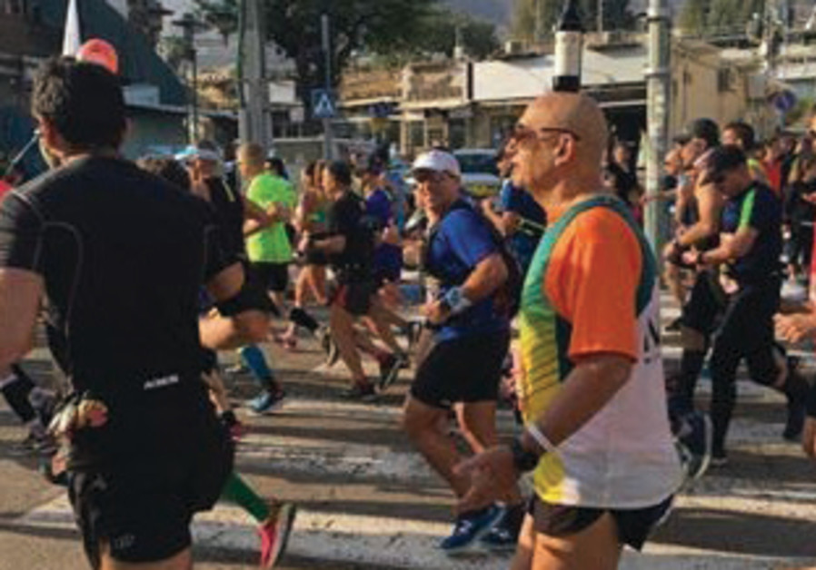 A man running with a wine bottle on his head during the Tiberias Marathon on January 5