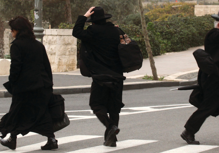 Haredi men hold on to their hats on a windy day in Jerusalem