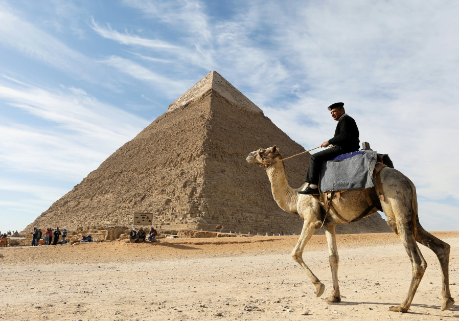 A police officer patrols the Giza Pyramids on his camel on the outskirts of Cairo, Egypt