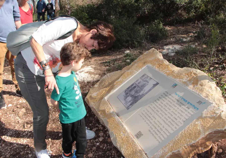 A mother and son look at an information board on the Bricha Trail