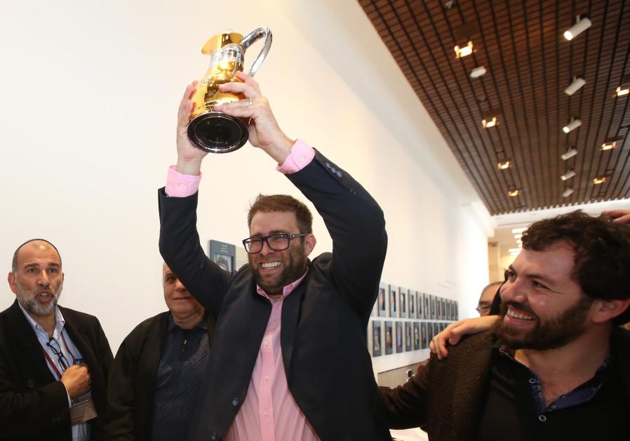 MK Oren Hazan hoists a trophy after winning the Knesset's backgammon tournament.