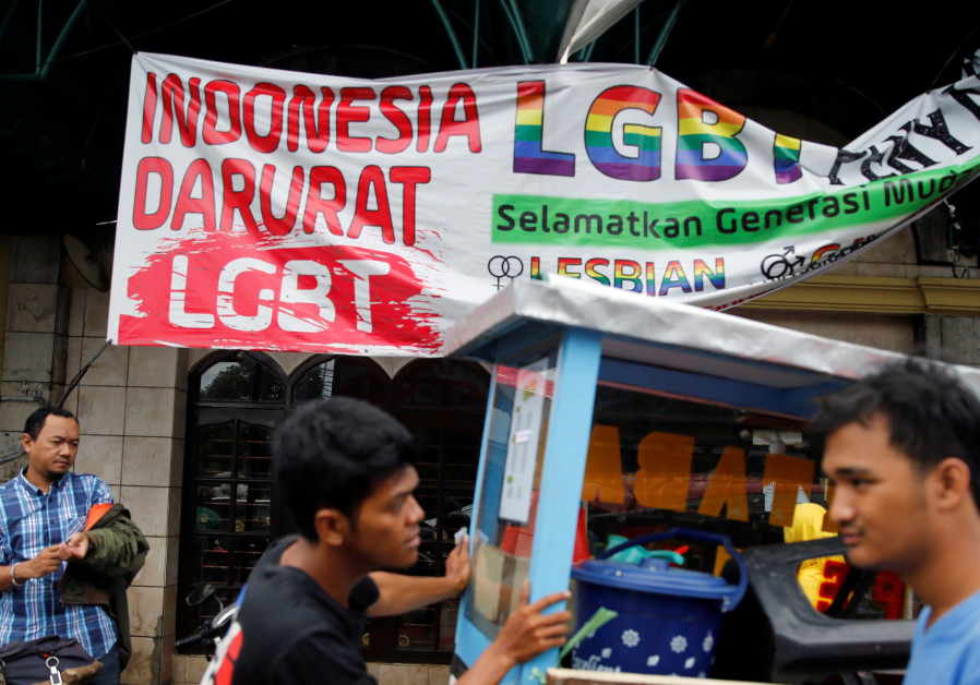 A street vendor walks past a banner reading 'Indonesia LGBT Emergency'