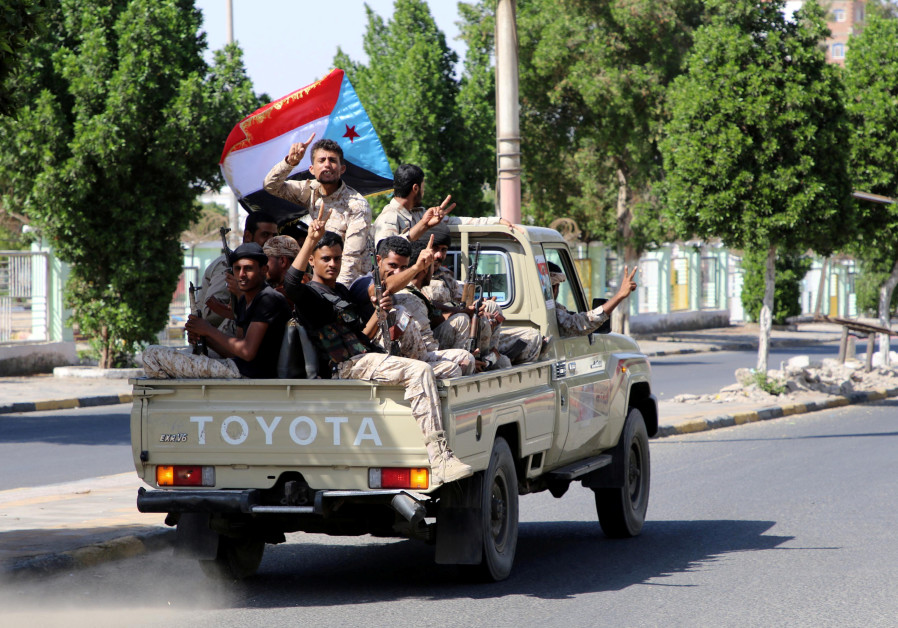 Southern Yemeni separatist fighters flash the V sign as they ride on the back of a truck in Aden