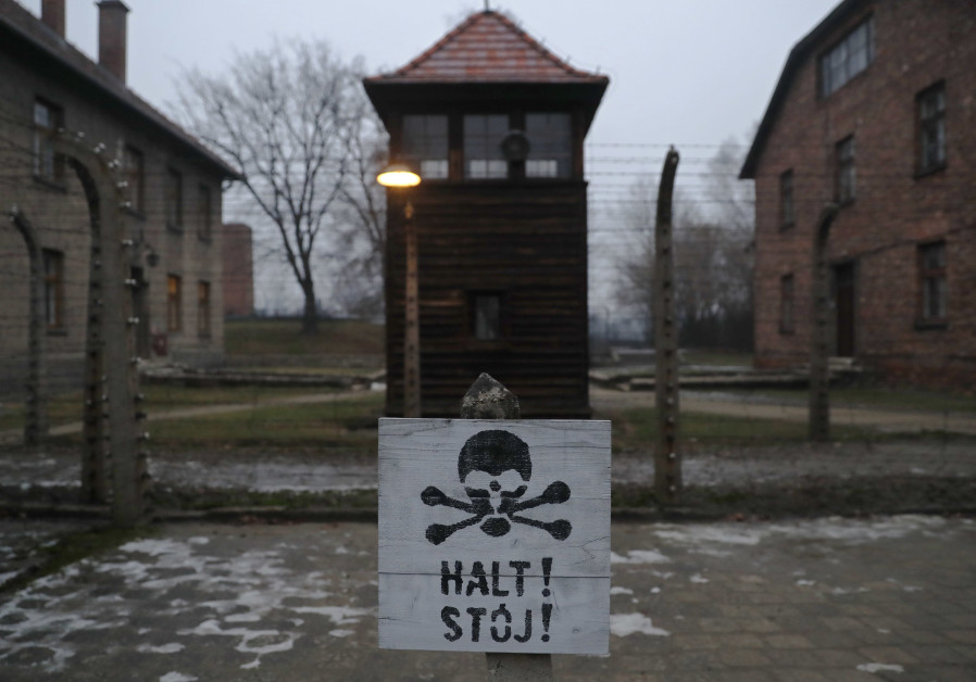 """A sign reading """"Stop"""" in German and Polish is placed outside the gates to Auschwitz to mark the anni"""