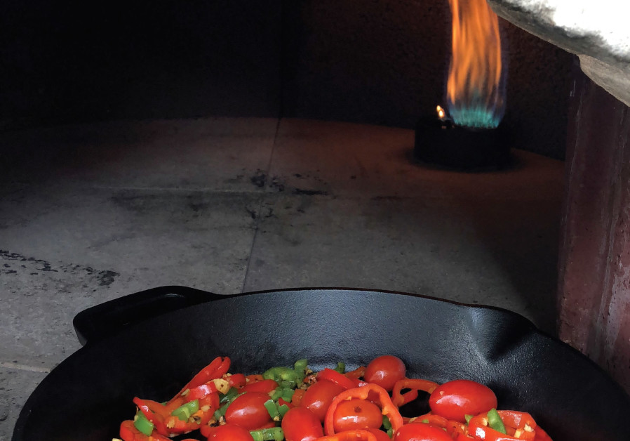 Tomatoes cooked on a skillet in a taboun.