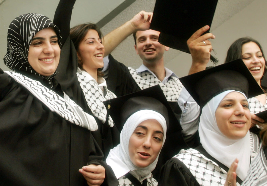 Palestinian students celebrate following a graduation ceremony at Al-Najah University in the West Ba