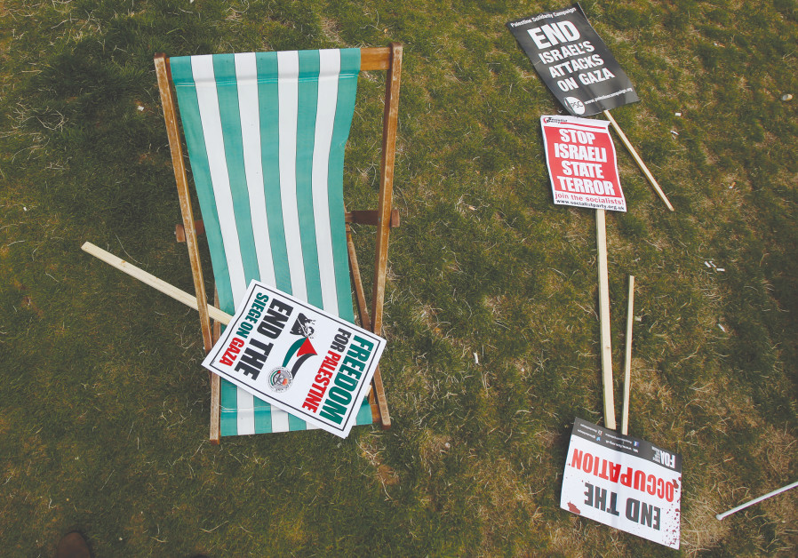 ANTI-ISRAEL SIGNS sit on a field after an anti-Israel rally in London