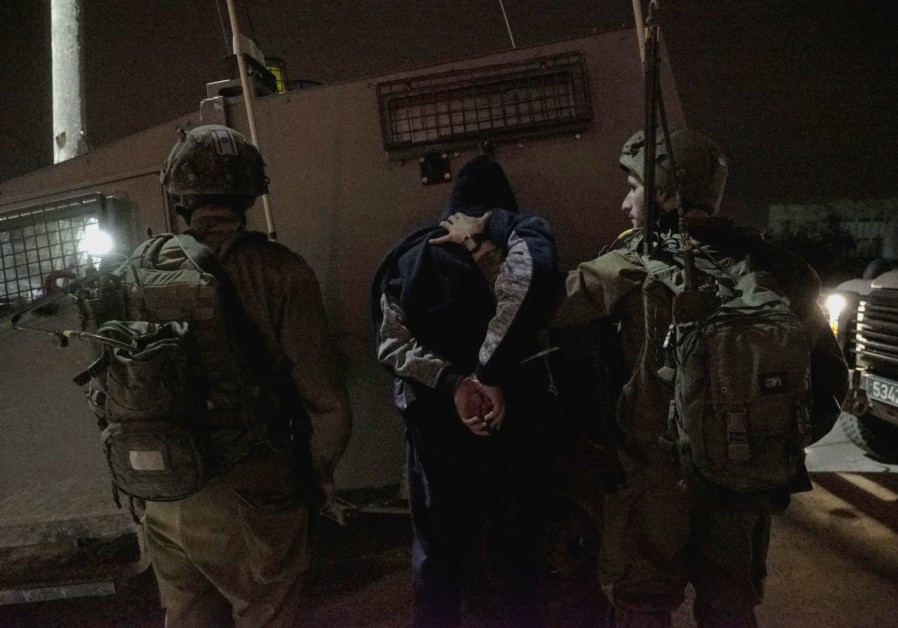 Israeli forces arrest a man in the West Bank village of Al-Yamun