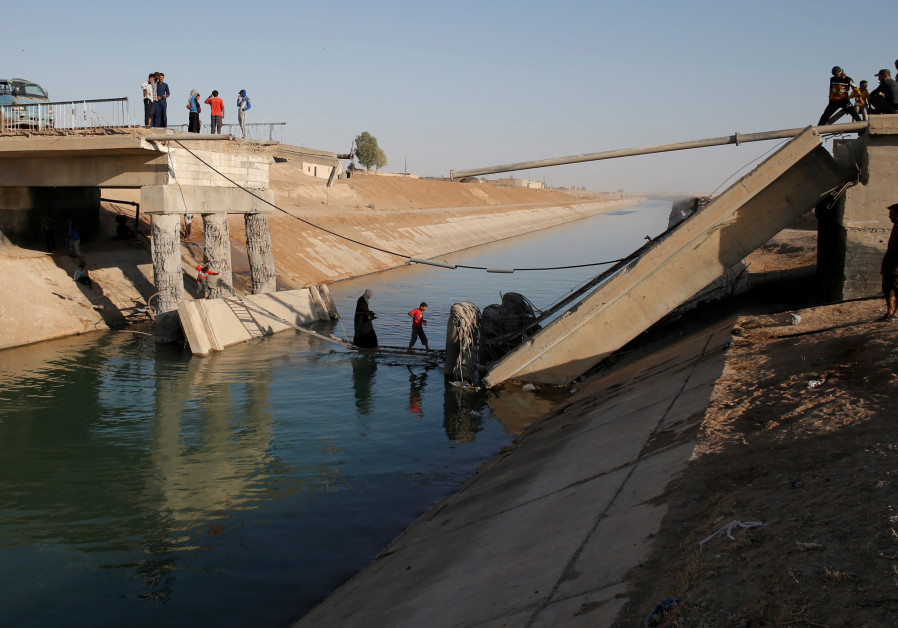 People cross a makeshift ladder in a village near Raqqa, Syria