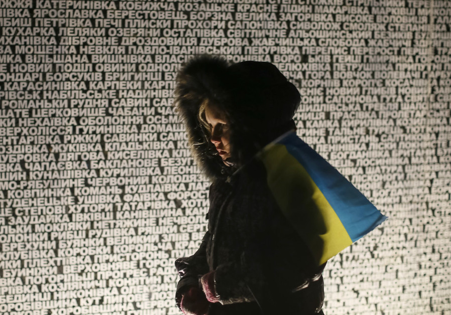 A girl holding a Ukrainian flag walks by a memorial commemorating the Holodomor