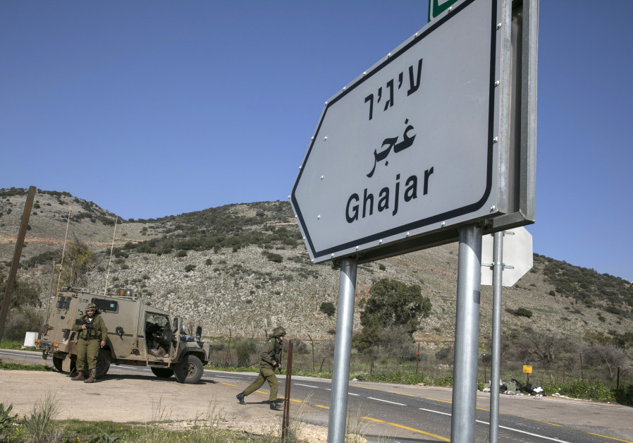 Israeli soldiers are seen next to a sign post pointing to the village of Ghajar near Israel's border
