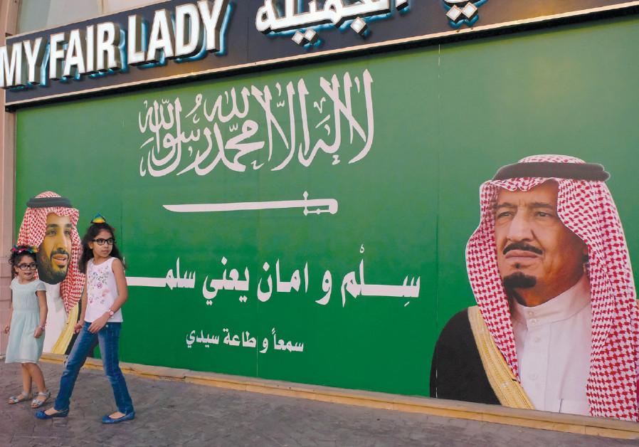 GIRLS STAND next to a poster depicting Saudi Arabia's King Salman bin Abdulaziz Al Saud (right) and