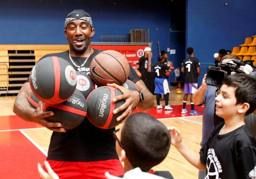 Former NBA player Amar'e Stoudemire smiles during a basketball workshop