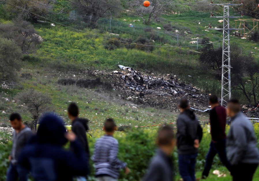 Bystanders look on at the remnants of an Israeli F-16 fighter jet shot down by Syrian forces, Februa