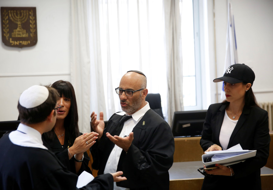 Yehuda Fried (C), lawyer of Malka Leifer, speaks to a state prosecutor (L) after a court session at