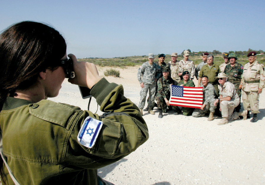 An Israeli soldier takes a photograph of paratroopers from around the world during a practice aerial
