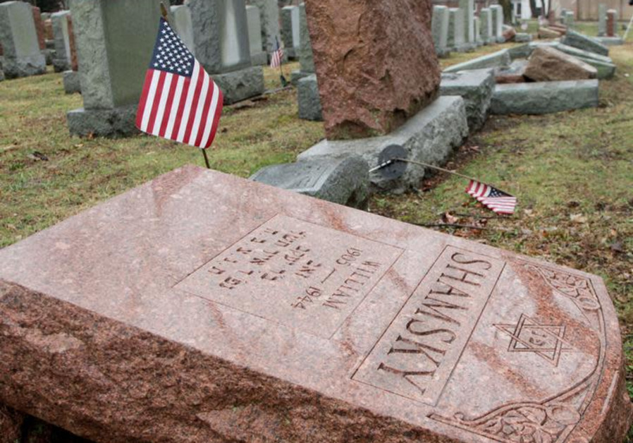An American flag still stands next to one of over 170 toppled Jewish headstones.