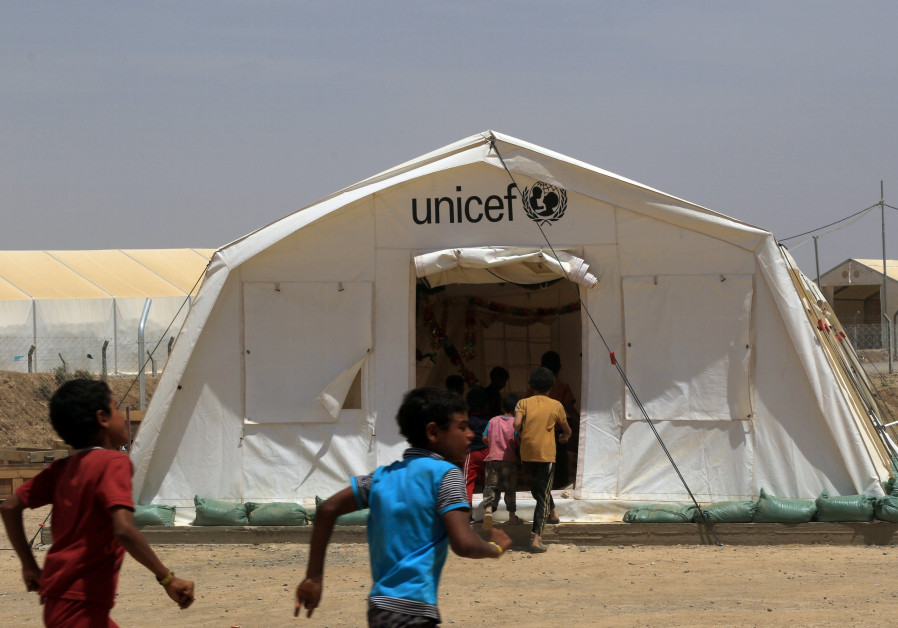 Displaced Iraqi boys enter a tent school set by United Nations Children's Fund (UNICEF)
