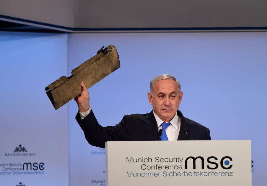 Prime Minister Benjamin Netanyahu holds up part of Iranian drone that landed in Israel in February 2018 at the Munich Security Conference, February 18, 2018. (Credit: Amos Ben Gershom/GPO)