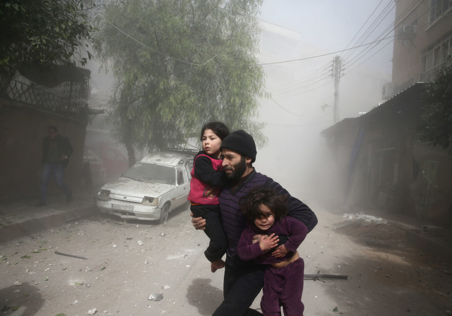 A man runs amid dust after an airstrike in the besieged town of Douma in eastern Ghouta in Damascus,